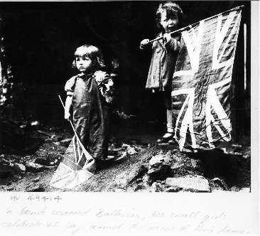 Two small girls celebrate VE Day amid the rubble.